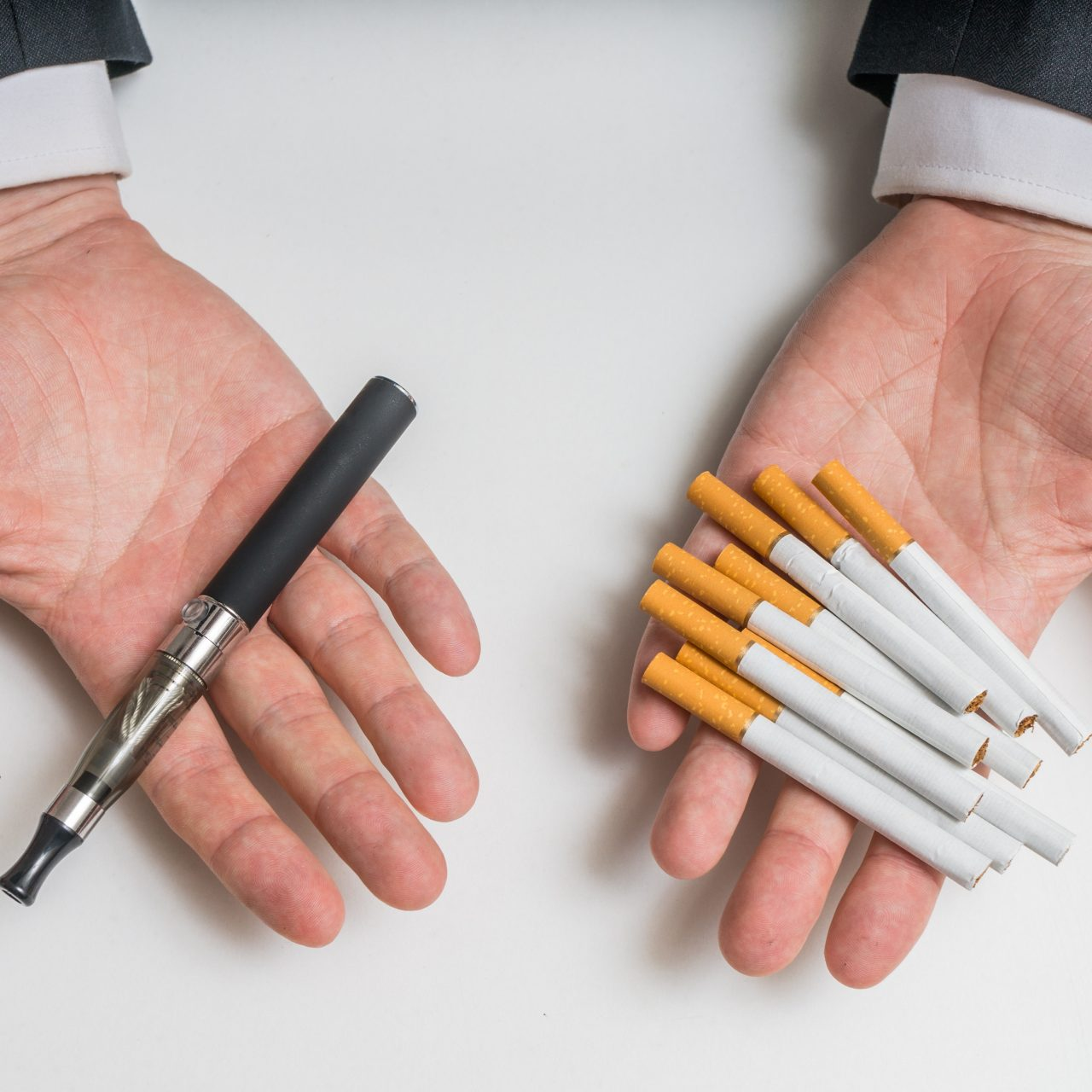 Hands are holding electronic vaporizer and conventional tobacco cigarettes and comparing them.